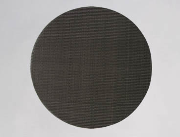 A circular multi layer extruder screen made of black wire cloth.