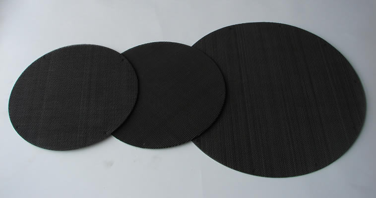 Three different sizes of black circular multi layer extruder screens made from black wire cloth.