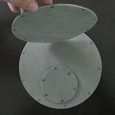 Two circular spot welded extruder screen packs flat on ground and another circular extruder screen pack upright on them.