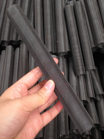 A single layer cylindrical extruder screen made of black wire cloth in one hand and others in paper carton.